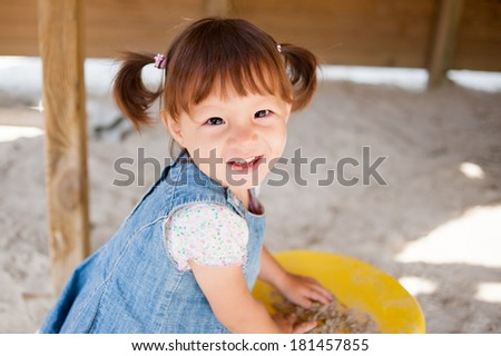 Happy little girl in playground - stock photo