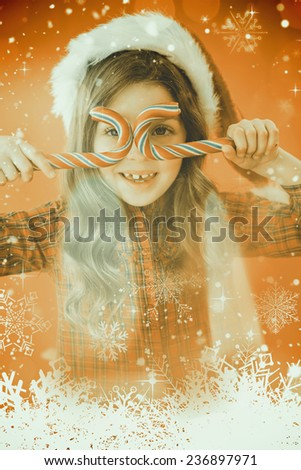 Happy little girl in santa hat holding candy canes against candle burning against festive background - stock photo