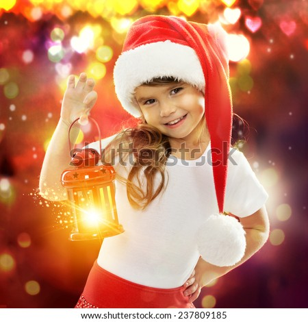 Happy little girl in Santa hat holding red Christmas lantern. With colorful lights on background. Holidays, christmas, new year, x-mas concept.