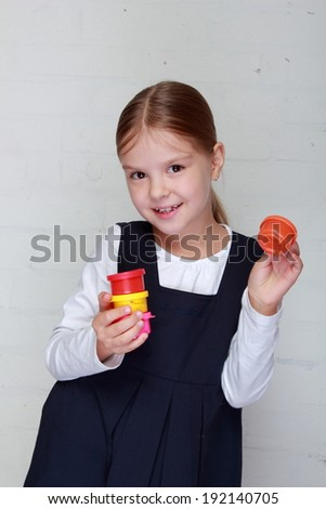Happy little girl in school uniform holding a tube of paint for painting on Education