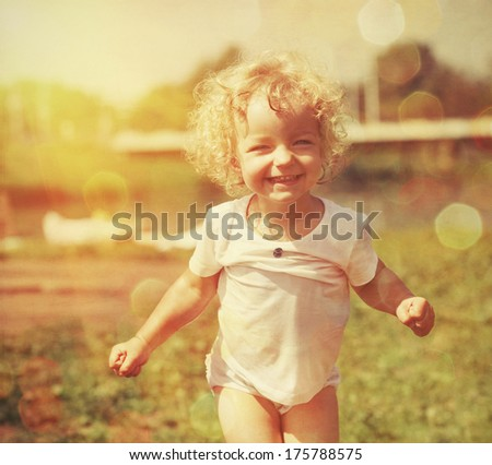 Happy little girl in summer sunlight. Vintage paper textured - stock photo
