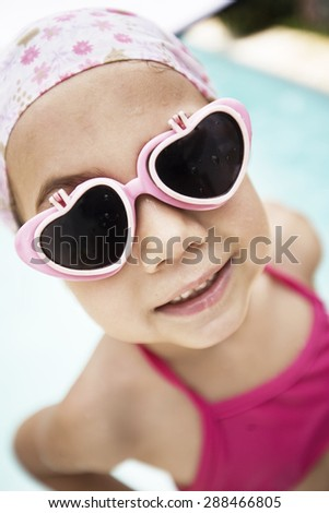 Happy little girl in swimming pool wearing sunglasses - stock photo