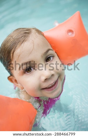 Happy little girl in swimming pool with floats - stock photo