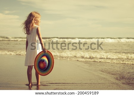 Happy little girl in the hat walking at the beach at the day time - stock photo