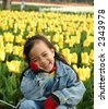 Happy little girl in tulips garden - stock photo