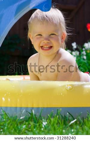 Happy little girl in yellow pool - stock photo