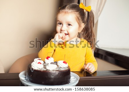 happy little girl indoors with a birthday cake