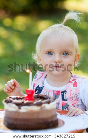 Happy little girl is celebrating her birthday outside in the park with cake. - stock photo
