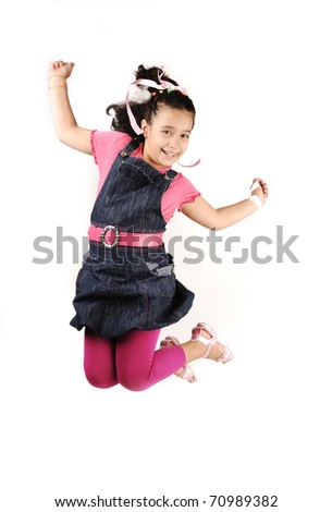 Happy little girl is jumping against white isolated background - stock photo