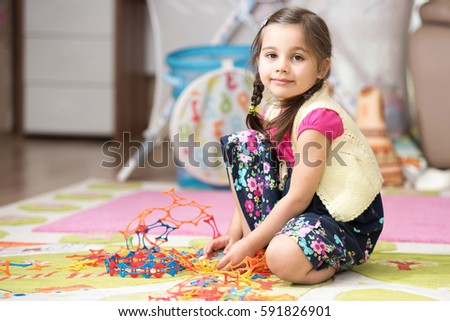 Happy Little Girl Is Playing With Toys At Home