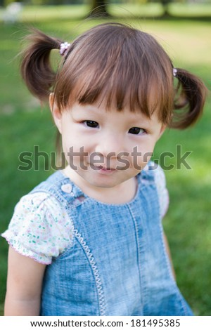 Happy little girl is posing in the park. - stock photo