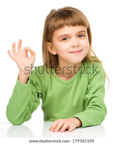 Happy little girl is showing OK sign, isolated over white - stock photo