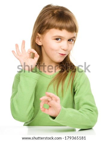 Happy little girl is showing OK sign using both hands, isolated over white - stock photo