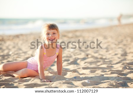 Happy little girl is sitting at the beach - stock photo