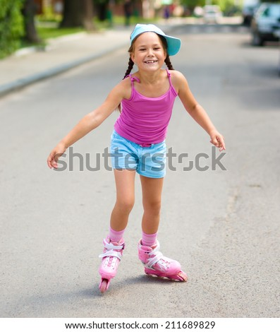 Happy little girl is skating on rollers, outdoor shoot - stock photo