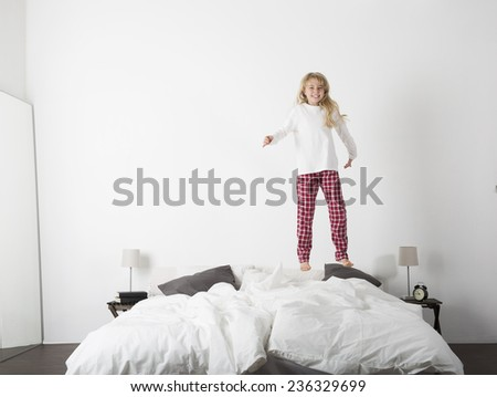 Happy Little Girl Jumping in bed with a smile on her face - stock photo