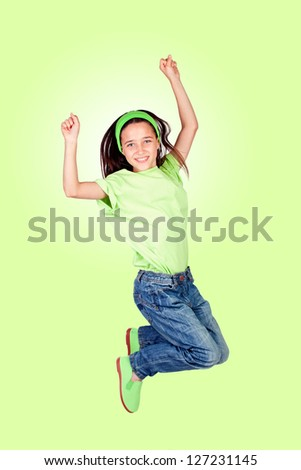 Happy little girl jumping isolated on a green background - stock photo