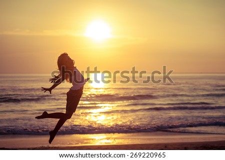 Happy little girl jumping on the beach at the sunset time - stock photo