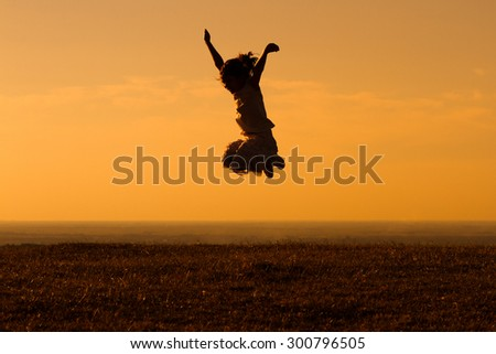Happy little girl jumping outdoor.Happy little girl - stock photo