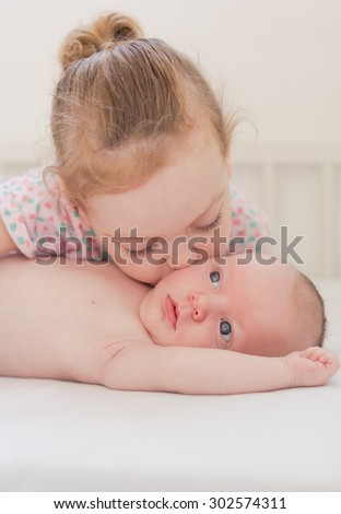 Happy little girl kissing her newborn brother - stock photo