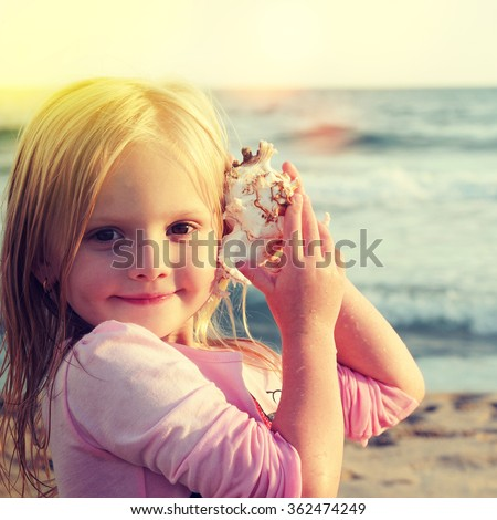 Happy little girl listen to seashell at the beach - stock photo