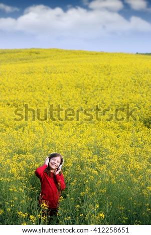 happy little girl listening music on field  - stock photo