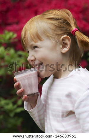 Happy little girl looking away while drinking smoothie at yard
