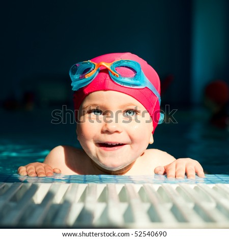 Happy little girl looking out from swimming pool - stock photo