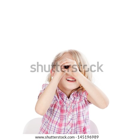 Happy little girl looking through hand telescope isolated over white background
