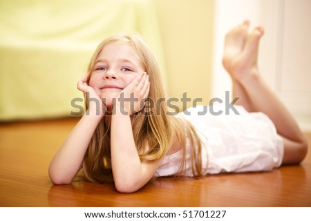 happy little girl lying on floor - stock photo