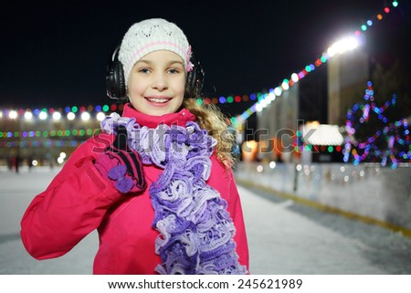 Happy little girl makes excellent gesture on the silent disco skating in the winter evening - stock photo