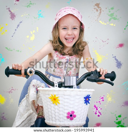 Happy little girl on a bicycle. Painted wall background. - stock photo