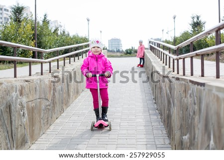 Happy little girl on a scooter in a park with a friend - stock photo