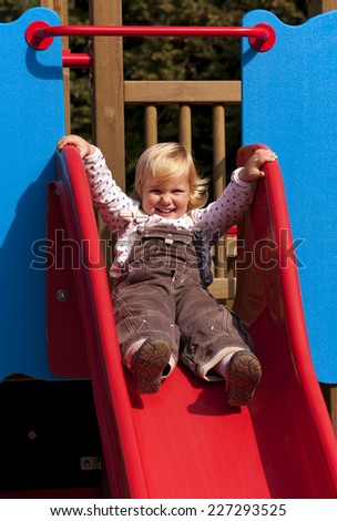 Happy little girl on slide - stock photo