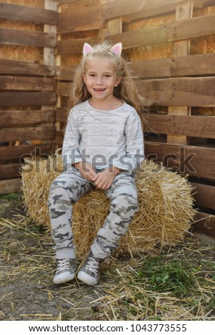 happy little girl on the hay in countryside