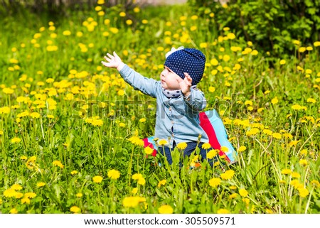 Happy little girl  on the meadow with dandelions - stock photo