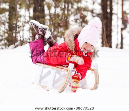 happy little girl on the sledge outdoor on a winter day - stock photo