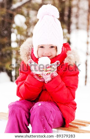happy little girl on the sledge with a snowball in her hands outdoor on a winter day - stock photo