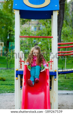 happy little girl on the slide at the playground - stock photo