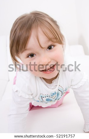 happy little girl on white sofa - stock photo