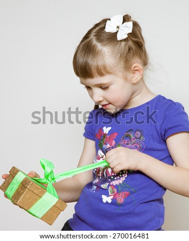 Happy little girl opening gift box, neutral background - stock photo