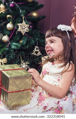 Happy little girl opening presents. Sitting near a Christmas tree decorated. The stylish interior decor. Merry Christmas and happy New Year! A series of photos
