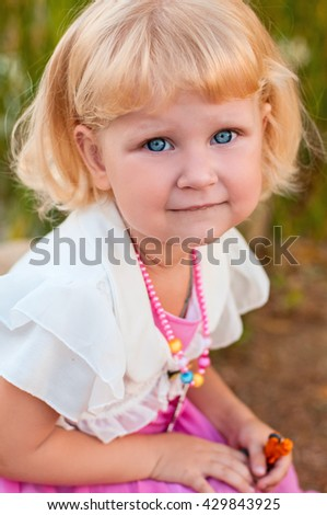 happy little girl outdoors in blooming park. Beautiful blonde girl playing in park. Cute little girl at the seaside in the summer.Adorable little girl at beach during summer vacation