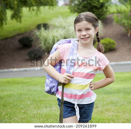 Happy little girl outside with backpack - stock photo