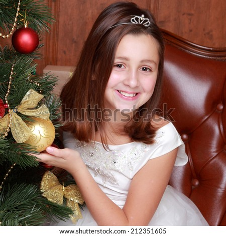 Happy little girl over christmas tree on Holiday theme/Pretty smiley princess in white dress