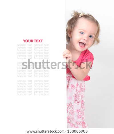 happy little girl peeking out from behind a white advertisement board - stock photo