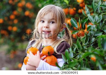 happy little girl picking fresh organic fruits on a farm - stock photo