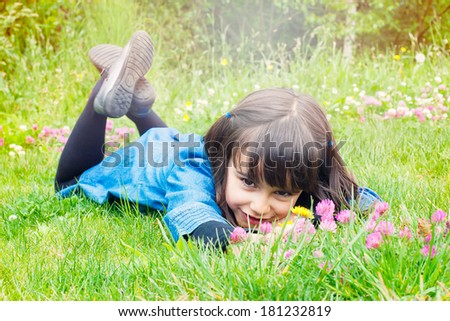 Happy little girl picking wild flowers lying in the grass - stock photo
