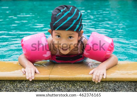Happy little girl plaing in swimming pool
