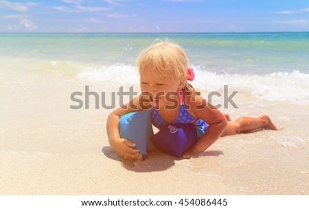 happy little girl play with armbands at sea